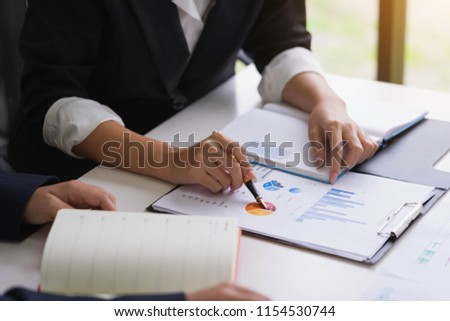 Business woman holding a pen pointing the graph and partnership to analyze the marketing plan with calculator on wooden table in office. #1154530744