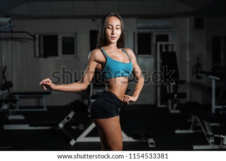 fitness girl exercising with barbell in gym, woman posing in gym #1154533381
