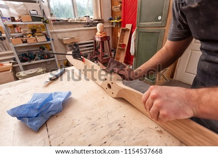 Close up of A man carpenter in a cap, goggles and a T-shirt is sanding a wooden  in the workshop, in the background a lot of tools  #1154537668