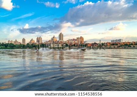 Kiev, Ukraine - July 13, 2018 - Wakeboarder on wakeboard going for behind boat at Kyiv Obolon embankment. View from water of Dnieper river. #1154538556