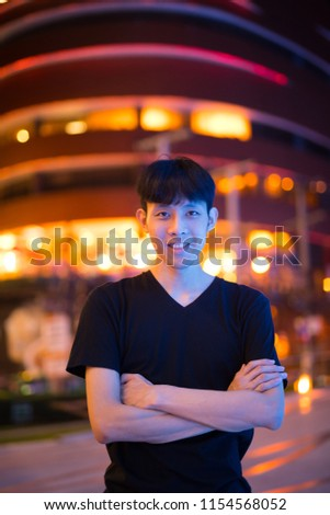 Portrait Of Asian Man Smiling Outdoors At Night #1154568052