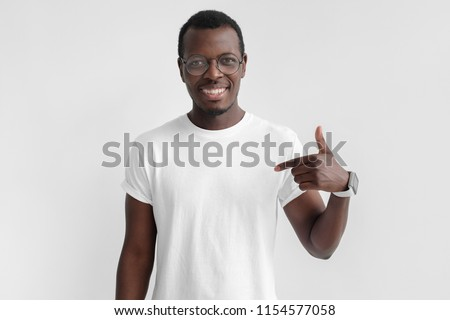 Indoor photo of young African American man pictured isolated on grey background pointing to his white blank T-shirt drawing attention to advertisement on it, promoting goods, apps or services