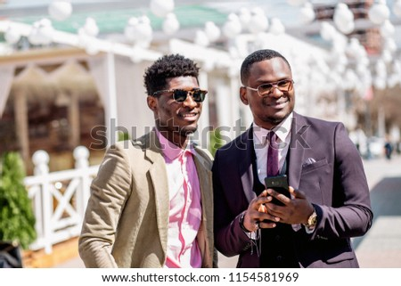 smiling smart businessmen standing outdoors andusing cell phone.close up side view photo. technology and communication concept. free time #1154581969