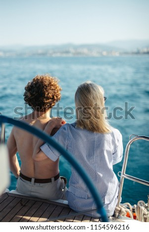 Young Couple Relaxing on a Yacht. Rear view of happy young caucasian curly man and his attractive girlfriend sitting on private boat duting sea trip. #1154596216
