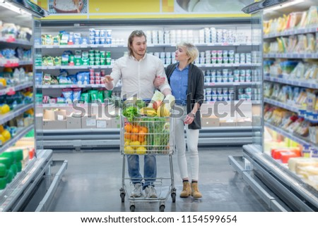 Positive family customers with full trolley of healthy organic vegetables and fruits in grocery store during weekly food shopping #1154599654