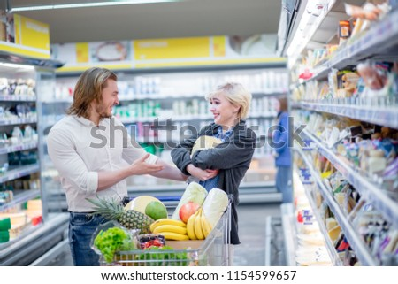 Consumerism concept. Ordinary aucasian family going among shelves with goods with full pushing cart with grocery goods, choosing dairy products and smiling in hypermarket #1154599657