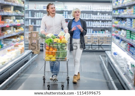 Caucasian cheerful male and female shoppers push cart with grocery products in supermarket aisle #1154599675