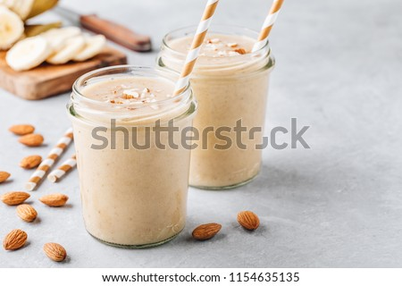 Healthy breakfast. Banana almond smoothie with cinnamon and oat flakes and coconut milk in glass jars #1154635135