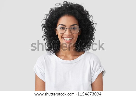Beautiful smiling African American female with crisp hair, broad smile, shows white teeth, wears casual t shirt and spectacles, stands over studio wall rejoices having day off. Woman journalist indoor #1154673094