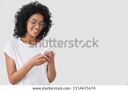 Cheerful African American with crisp hair, holds modern smart phone, happy to recieve message, dressed in casual t shirt, poses against white background with blank space for your advertisement #1154675674