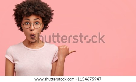 Omg concept. Stupefied dark skinned female with surprised expression, opens eyes and mouth widely, points aside with thumb, shows something strange on pink background. Advertisement concept. Royalty-Free Stock Photo #1154675947
