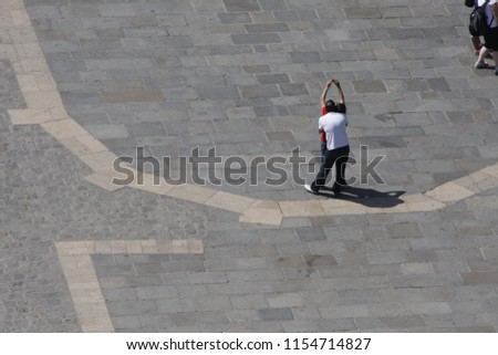 Paris / France - June 23, 2010: A couple is standing on a square near Notre-Dame-de-Paris, a man is embracing a woman, she's making selfie with a small photo-camera. #1154714827