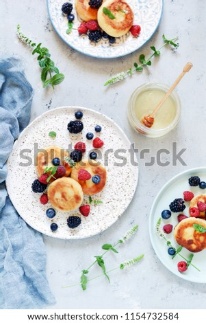 Sunday breakfast with cheesecake, honey, fresh berries  and mint. Cottage cheese pancakes or curd fritters decorated honey and berries in plate on blue table top view. Healthy and diet breakfast. #1154732584