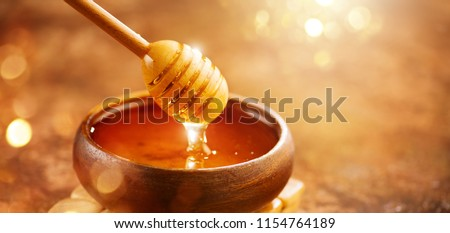 Honey dripping from honey dipper in wooden bowl.  Close-up. Healthy organic Thick honey dipping from the wooden honey spoon, closeup. #1154764189