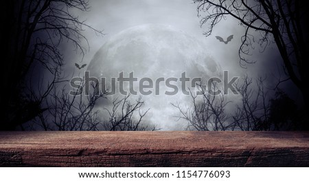 Old wood table and silhouette dead tree at night for Halloween background. #1154776093