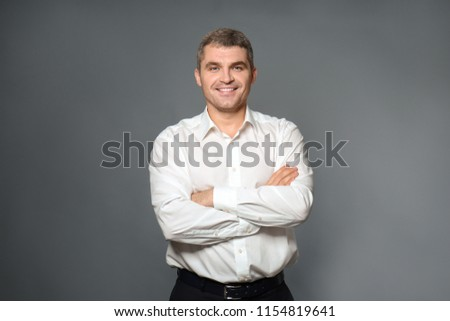 Handsome confident businessman on grey background #1154819641
