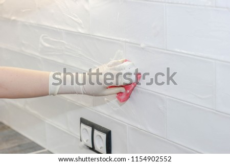 washing and cleaning ceramic white tiles on the wall in the kitchen. #1154902552