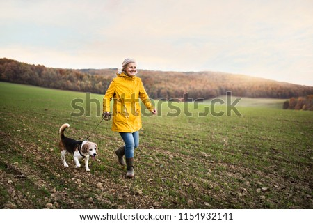 Senior woman with dog on a walk in an autumn nature. #1154932141