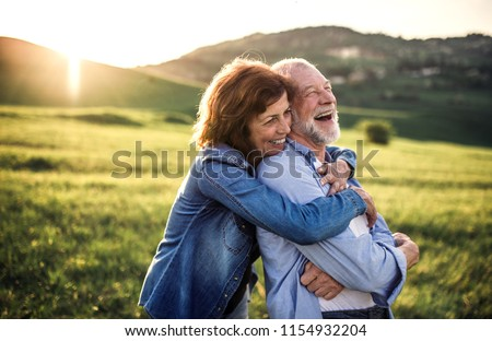Side view of senior couple hugging outside in spring nature at sunset. #1154932204