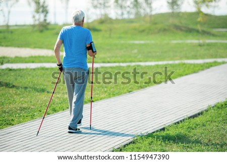 Back view portrait of active senior man practicing Nordic walking with poles outdoors in park, copy space #1154947390