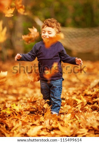 Picture of pretty baby boy running in autumnal park, little child playing with old dry trees foliage, adorable toddler play game on backyard, enjoying walk, beauty autumn season, happy childhood