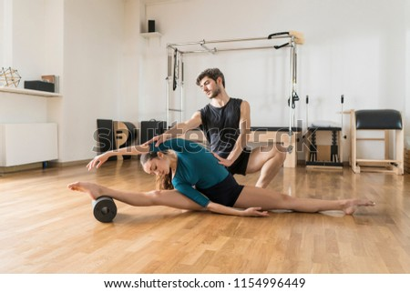 Pilates instructor coaching using foam roller #1154996449