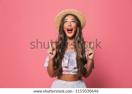 Portrait of happy brunette woman 20s wearing straw hat screaming and pointing fingers upward isolated over pink background in studio #1155030646
