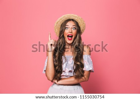 Portrait of pretty glamour woman 20s wearing straw hat screaming and pointing finger upward isolated over pink background in studio #1155030754