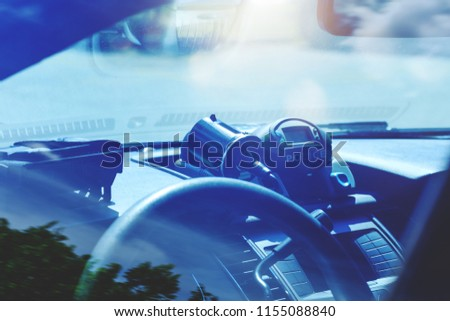 Police radar inside of car. Patrol monitors traffic on a highway or on the roads of municipal district. Modern speed trap at a road. Policemen in the supervise activity of the transport in traffic.