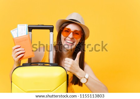 Traveler tourist woman in summer casual clothes, hat with suitcase showing thumb up isolated on yellow background. Passenger traveling abroad to travel on weekends getaway. Air flight journey concept #1155113803