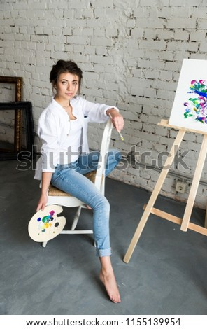 Gorgeous and sensuality young female artist sitting on chair near window and drawing picture with oil colorful paints. Beautiful brunette girl in white shirt and jeans with dirty hands after work. #1155139954