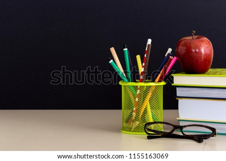 Back to school supplies. Books and red apple on dark background. Still life. Copy space. #1155163069