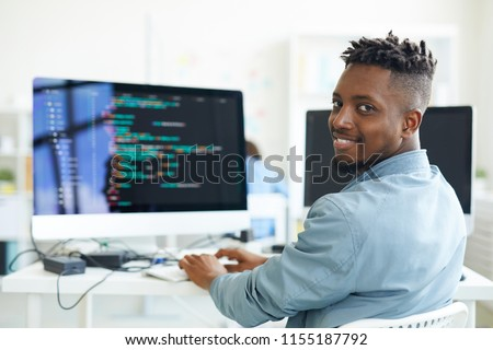Happy guy looking at you while sitting by workplace and working with software #1155187792