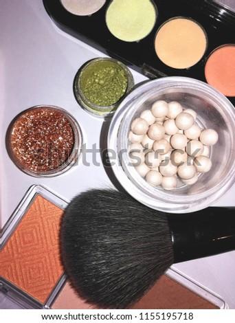 Cosmetics: powder, colorful eyeshadows, blusher at the light background #1155195718