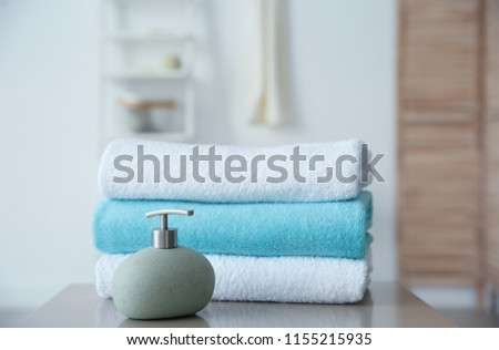 Clean towels and soap dispenser on table against blurred background #1155215935