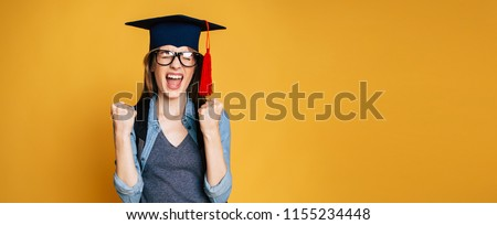 Study, education, university, college, graduate concept on yellow banner. Happy and excited portrait of young blond student girl in hat of graduation isolated  Royalty-Free Stock Photo #1155234448