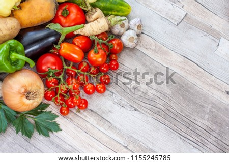 Colourful variety of fresh home grown vegetables from an organic garden on a wooden surface. Tomato, green and yellow bell peppers, carrot, parsley, onion, garlic, potato, eggplant and zucchini. #1155245785