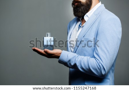 Male holding up bottle of perfume. Man perfume, fragrance. Perfume or cologne bottle and perfumery, cosmetics, scent cologne bottle, male holding cologne. Masculine perfume, bearded man in a suit. #1155247168