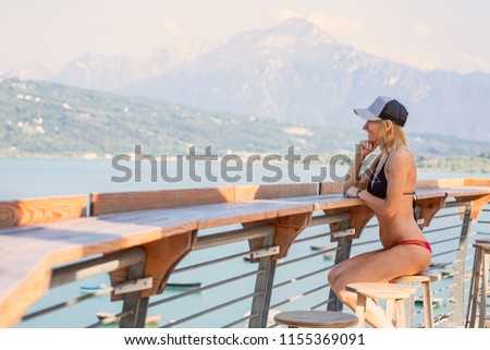 The beautiful young woman sits on a stool near the lake #1155369091
