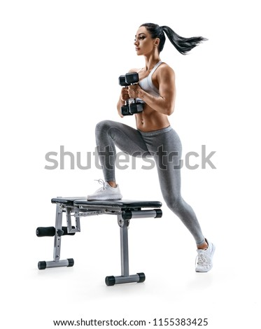 Fitness woman doing jump step ups exercise with dumbbells on bench. Photo of attractive woman in sportswear isolated on white background. Strength and motivation #1155383425