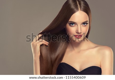 Beautiful model girl with shiny brown and straight long  hair . Keratin  straightening . Treatment, care and spa procedures. Smooth hairstyle. Care and beauty  products .  Royalty-Free Stock Photo #1155400609