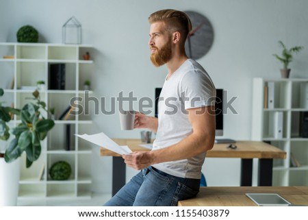 Bearded young businessman working at modern office.Man making notes on the documents. #1155403879