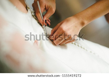 Bride getting ready, they help her by buttoning the buttons on the back of her dress. #1155419272