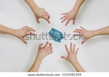 Top view on hands reaching for coupons at a discount. The concept of price reductions, discounts, sales. People want to buy cheap in the store. Fight for discount coupons. #1155485344