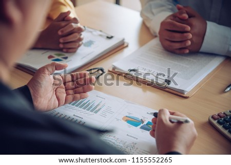Business team is working on accounting documents and team work together to present the work and help solve the problem.  #1155552265