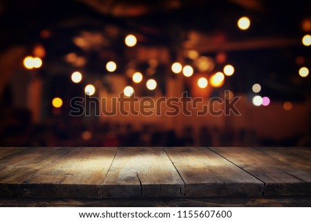 Image of wooden table in front of abstract blurred restaurant lights background #1155607600