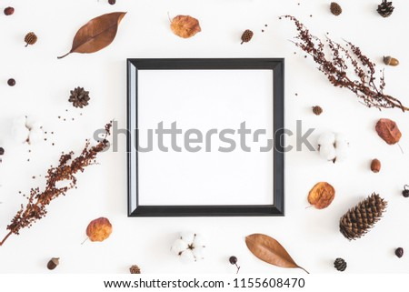 Autumn composition. Photo frame, dried flowers and leaves on white background. Autumn, fall concept. Flat lay, top view, copy space