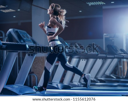 Woman trains on a treadmill in the gym. Young fitness girl running on treadmill machine. Sports exercises for weight loss. #1155612076