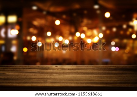 Image of wooden table in front of abstract blurred restaurant lights background. #1155618661