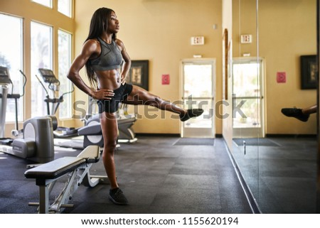 fit african american woman working out and stretching in gym #1155620194